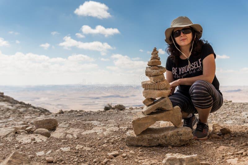 Una giovane donna si siede appoggiandosi il suo ginocchio vicino a parecchie pietre ha impilato uno sopra l'altro nel deserto di  fotografia stock