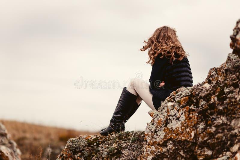 Una giovane donna si siede con lei di nuovo alla macchina fotografica sulle rocce immagini stock