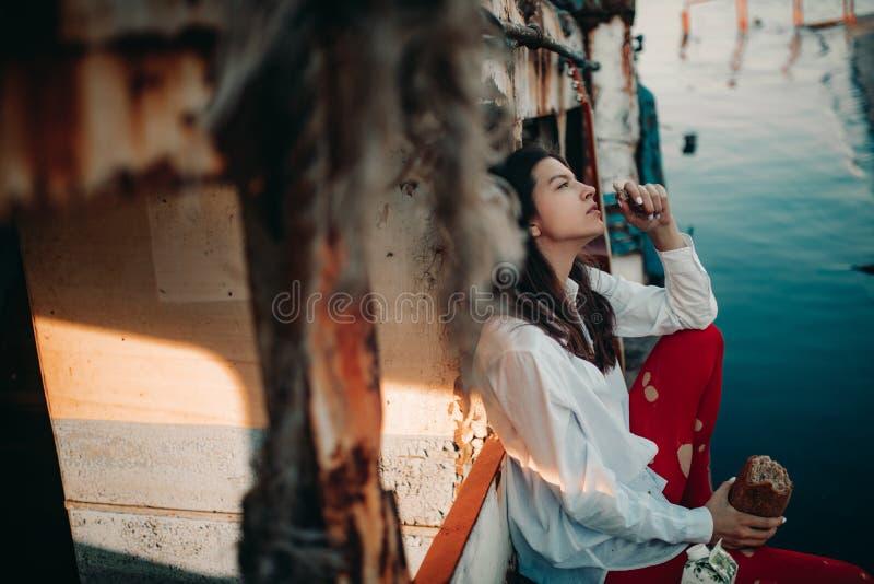 Una giovane donna si siede e mangia il pane su una vecchia nave abbandonata immagine stock libera da diritti