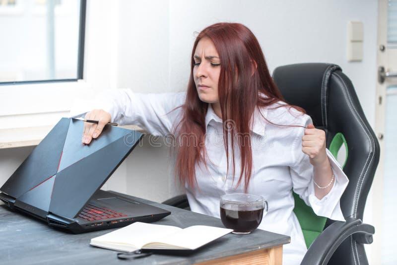 Una giovane donna sollecitata e arrabbiata sta sedendosi al suo scrittorio e sta chiudendo il suo computer portatile con una rabb immagine stock