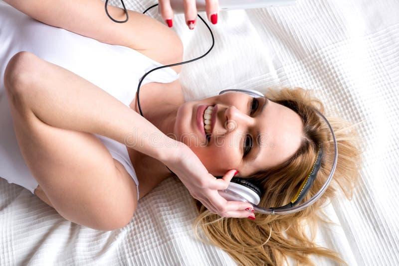 Una giovane donna sorridente che si trova su un letto e che ascolta la musica fotografia stock