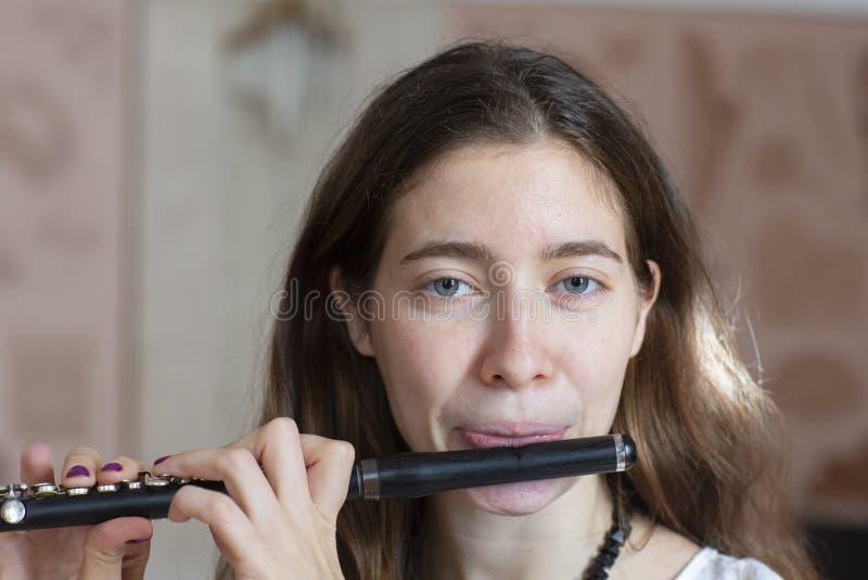 Una giovane donna splendida che si siede e che gioca l'ottavino della flauto fotografia stock