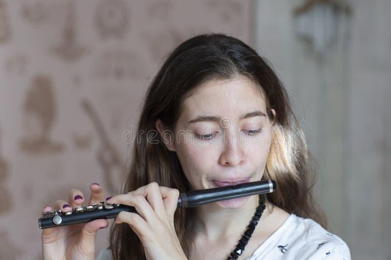 Una giovane donna splendida che si siede e che gioca l'ottavino della flauto fotografia stock libera da diritti