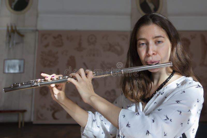 Una giovane donna splendida che si siede e che gioca la flauto fotografia stock