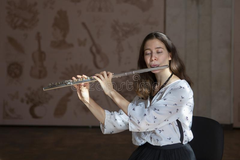 Una giovane donna splendida che si siede e che gioca la flauto fotografia stock libera da diritti