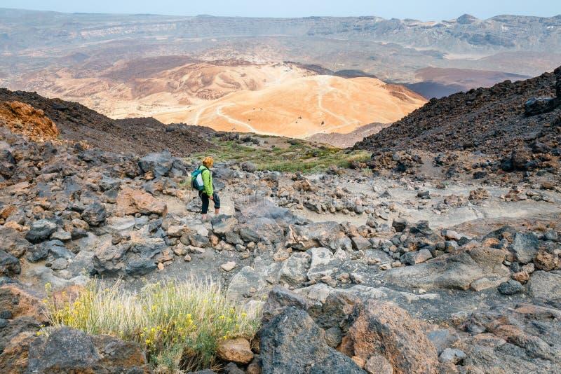Una giovane donna sta camminando nelle montagne fotografia stock libera da diritti