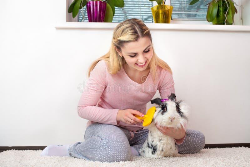 Una giovane donna sta pettinando il suo coniglio Animali domestici adorabili immagini stock libere da diritti