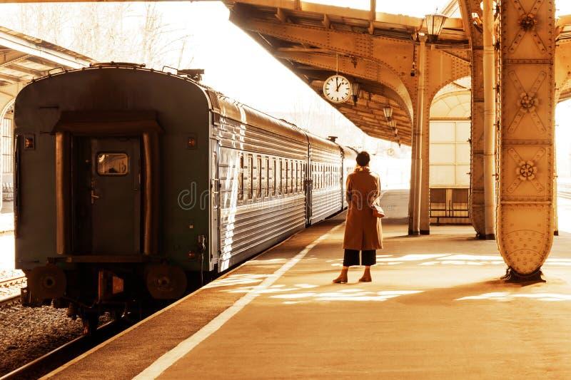 Una giovane donna sta sul binario sotto l'orologio della stazione fotografia stock libera da diritti