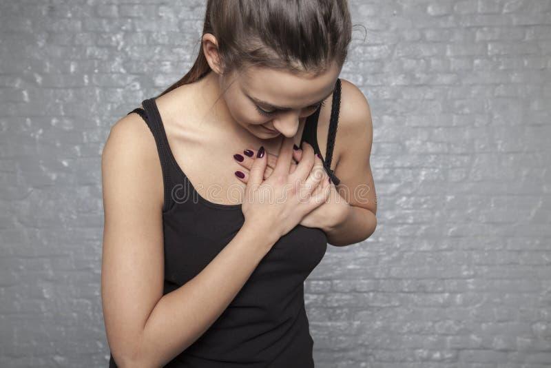 Una giovane donna sta tenendo il suo petto, attacco di cuore o oth possibile immagine stock libera da diritti