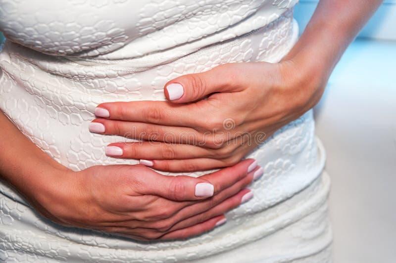 Una giovane donna tiene le sue mani sul suo stomaco Il concetto di IVF, gravidanza, digestione, la salute del sistema riproduttiv fotografie stock