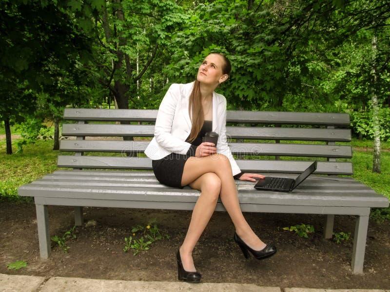 Una giovane donna tiene un vetro di caffè in sua mano e cerca mentre si siede su un banco con le sue gambe attraversate Concetto  immagini stock