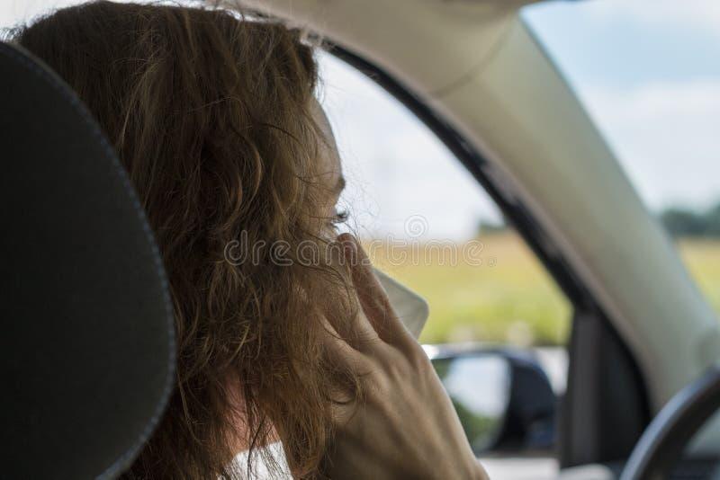 Una giovane donna in un'automobile parla sul telefono ed è distratta immagini stock