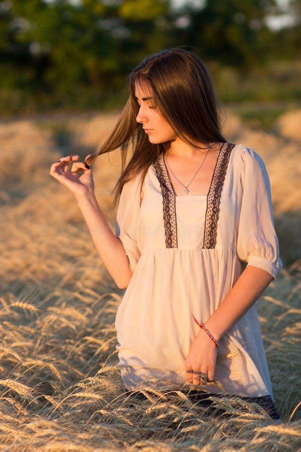 Una giovane donna in un bianco lungo ha ricamato la camicia in un prato alla s immagini stock