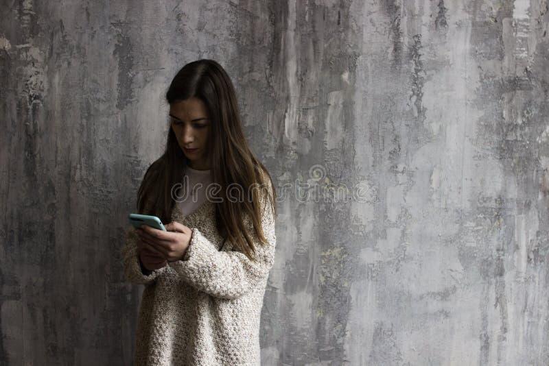 Una giovane donna in un cardigan beige che guarda nel telefono immagini stock