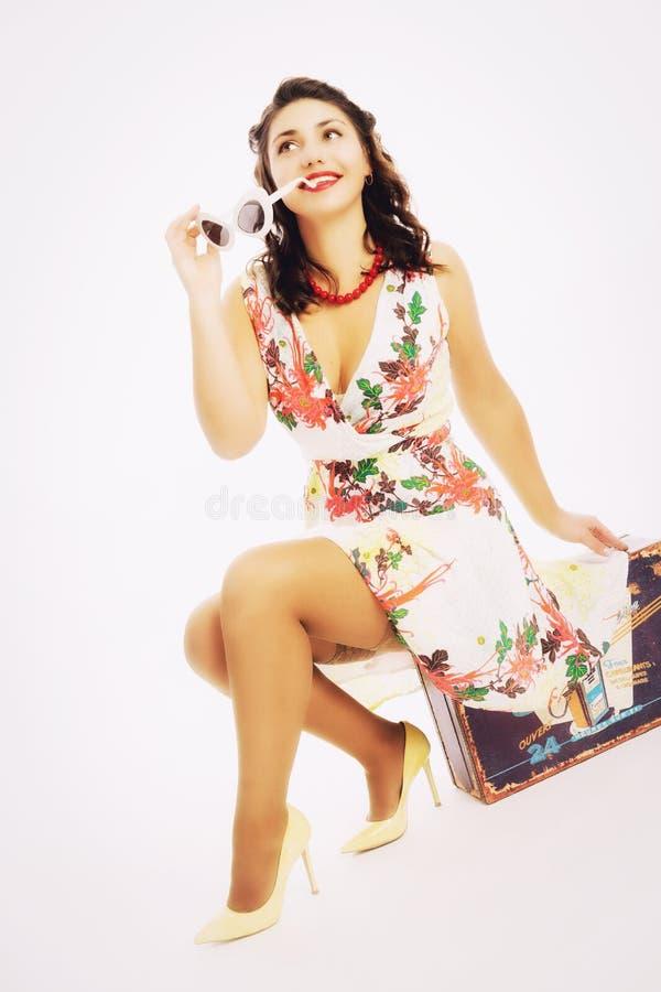 Una giovane donna in un vestito luminoso si siede su una valigia e sui sogni immagine stock libera da diritti