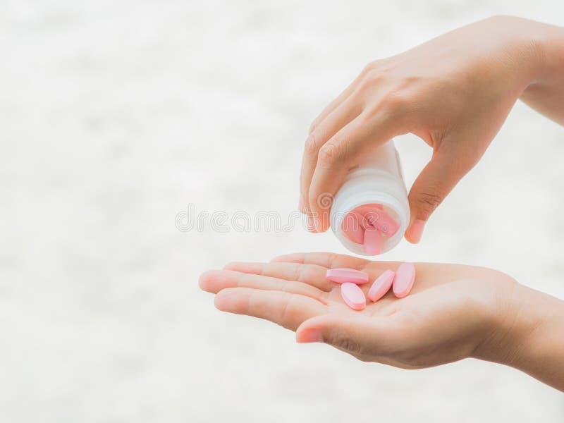 Una giovane donna versa fuori la medicina nella sua mano fotografia stock libera da diritti