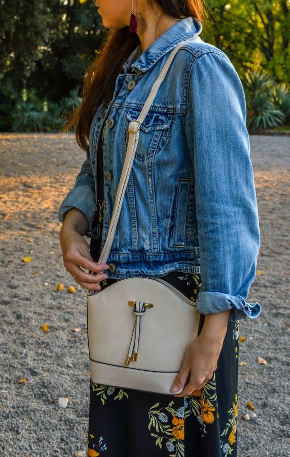 Una giovane donna, vestita con indifferenza, con una mini borsa sopra la sua spalla fotografia stock