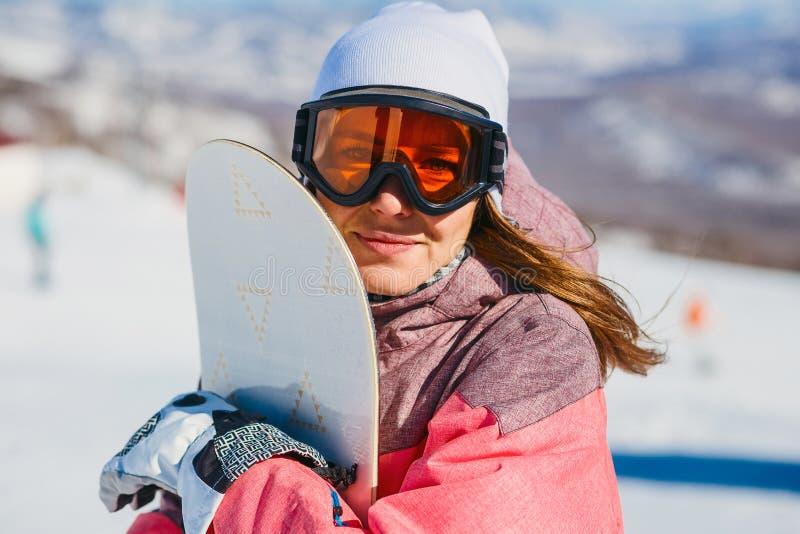 Una giovane donna in vetri con lo snowboard arancio dello sci immagine stock