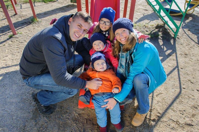 Una giovane famiglia di cinque sorridente felice al campo da giuoco del ` s dei bambini in parco fotografia stock
