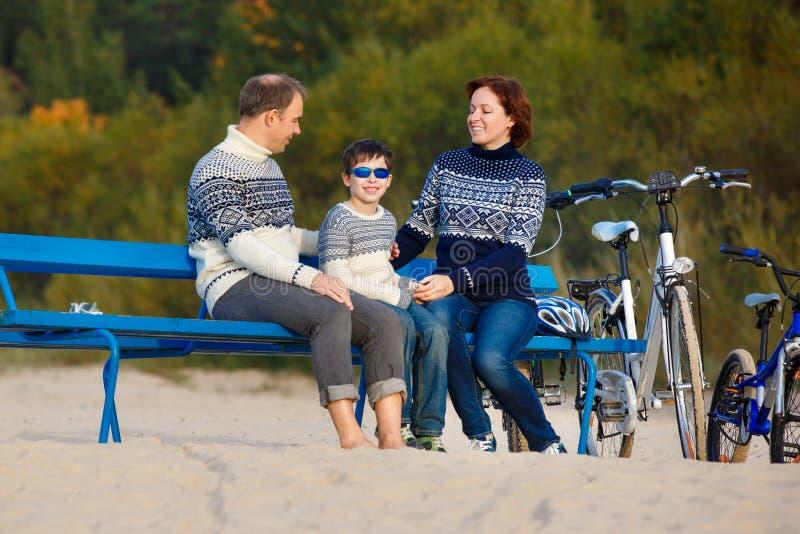 Una giovane famiglia di tre che hanno resto sul banco durante la loro guida della bici sulla spiaggia fotografia stock libera da diritti