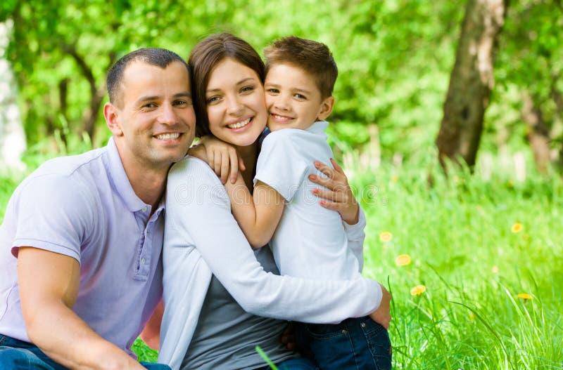 Una giovane famiglia di tre ha picnic in parco fotografia stock