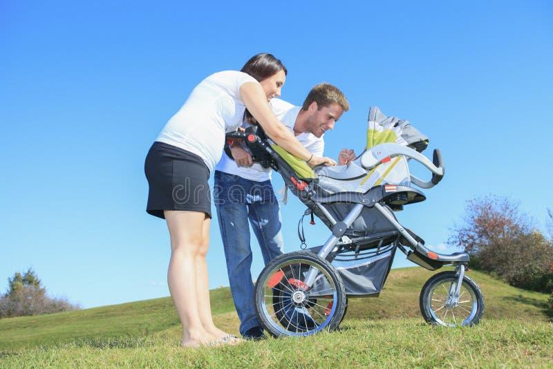 Una giovane famiglia felice con il piccolo neonato all'aperto fotografia stock