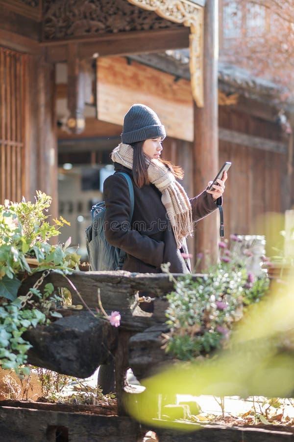Una giovane felice viaggiatrice che usa il cellulare o scaffale per fotografare la città vecchia di Lijiang, punto di riferimento fotografia stock