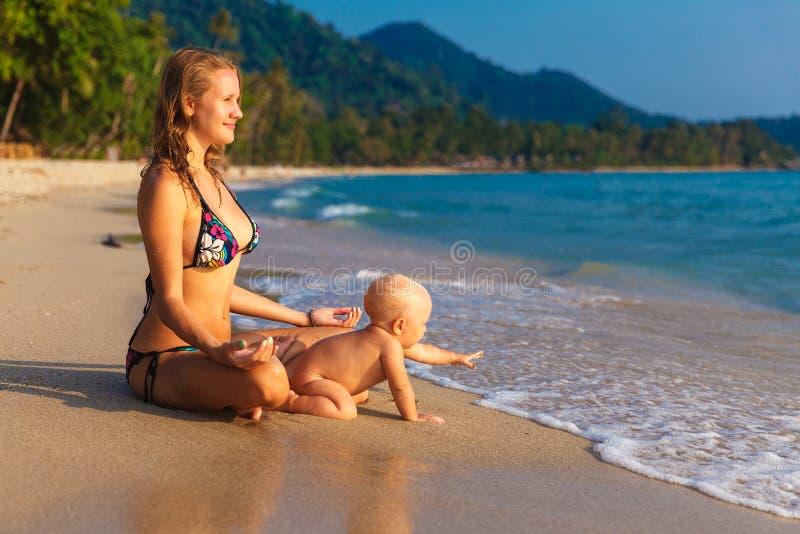 Una giovane madre con un bambino divertendosi su una spiaggia tropicale nazioni fotografia stock libera da diritti