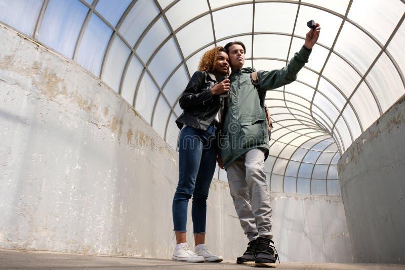 Una giovane ragazza afroamericana e un tipo europeo fanno un salfi con una piccola macchina fotografica di azione La gente dentro immagini stock libere da diritti