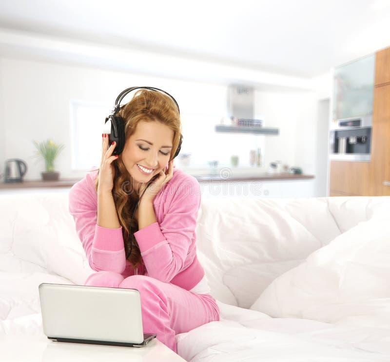 Una giovane ragazza attraente che ascolta la musica nell'interno moderno fotografie stock libere da diritti