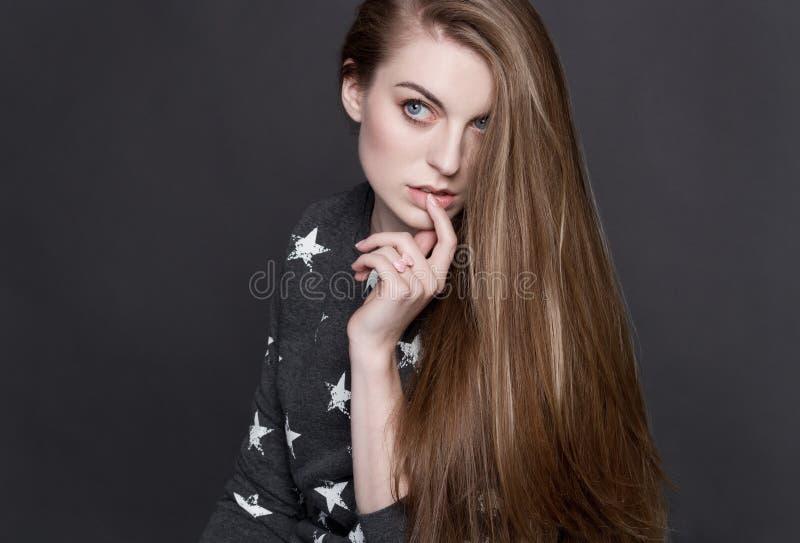 Una giovane ragazza bionda timida in un maglione grigio Sensuale tocca le sue labbra con il suo dito fotografia stock