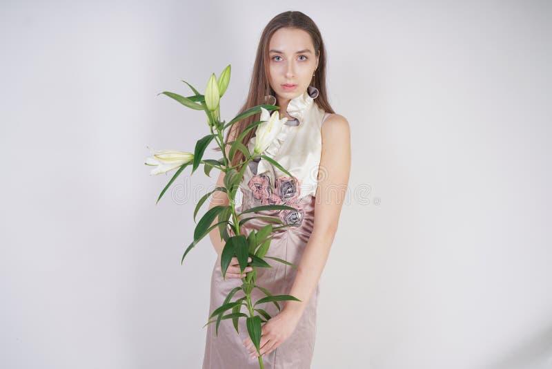 Una giovane ragazza caucasica affascinante sta in un breve vestito pallido delicato da promenade con l'applicazione dei fiori e p fotografia stock