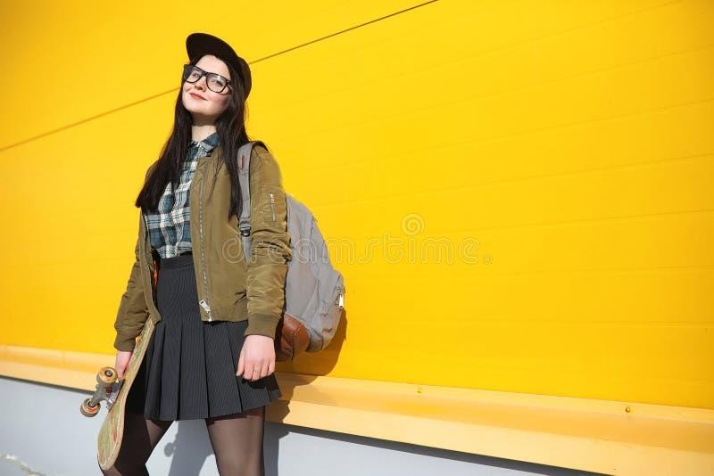 Una giovane ragazza dei pantaloni a vita bassa sta guidando un pattino Amiche f delle ragazze immagine stock
