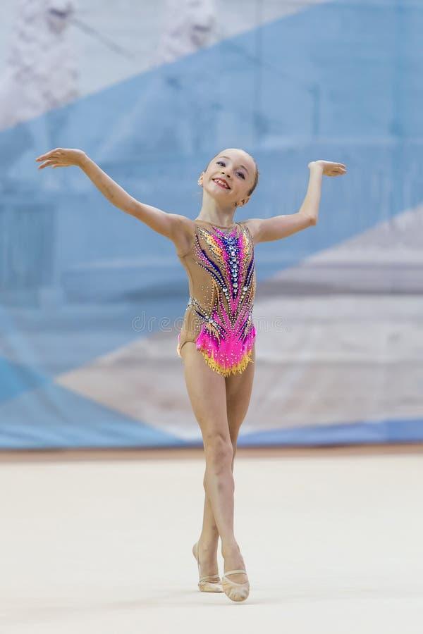 Una giovane ragazza dell'adolescente esegue ai concorsi in ginnastica ritmica fotografia stock libera da diritti