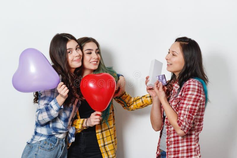 Una giovane ragazza felice prende un regalo di festa dai suoi amici su un fondo grigio neutrale fotografia stock