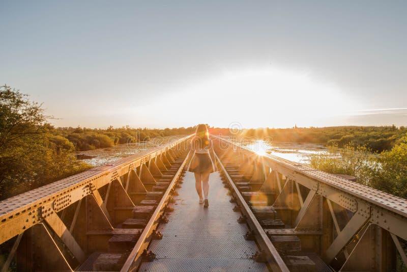 Una giovane ragazza snella felice cammina vicino ad un ponte nei raggi del sole dell'estate fotografia stock