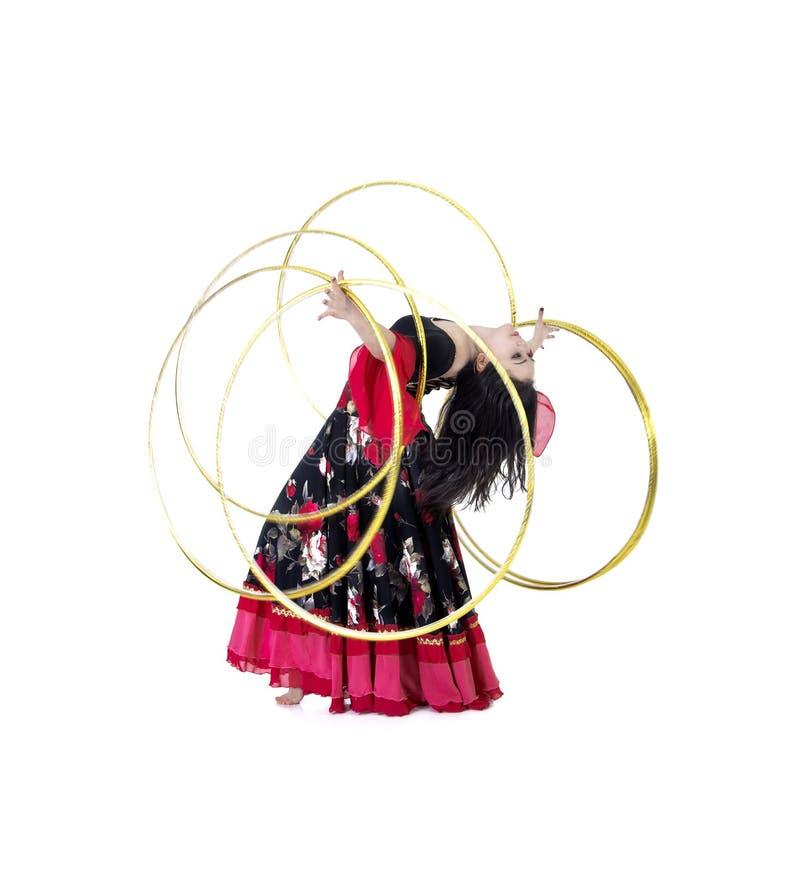 Una giovane, ragazza sorridente in un dancing lungo della gonna con un cerchio fotografia stock