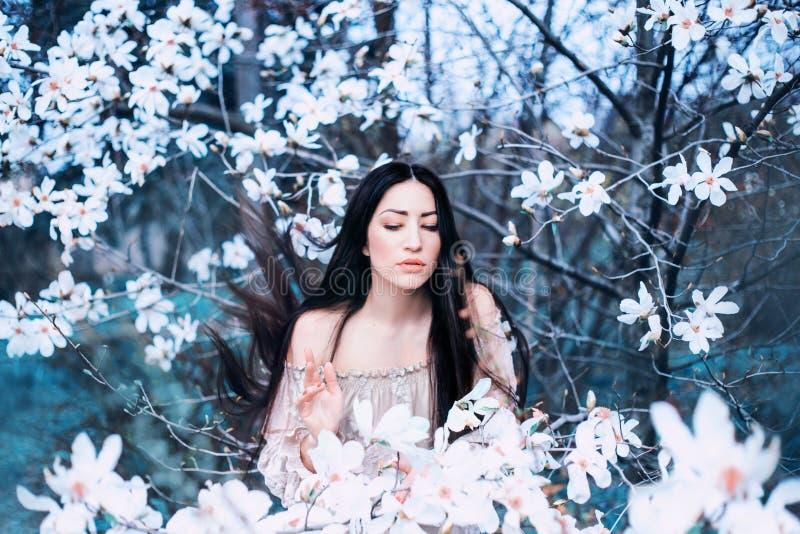 Una giovane signora mora deliziosa con gli occhi chiusi, supporti nel giardino delle magnolie di fioritura i capelli volano su co immagine stock