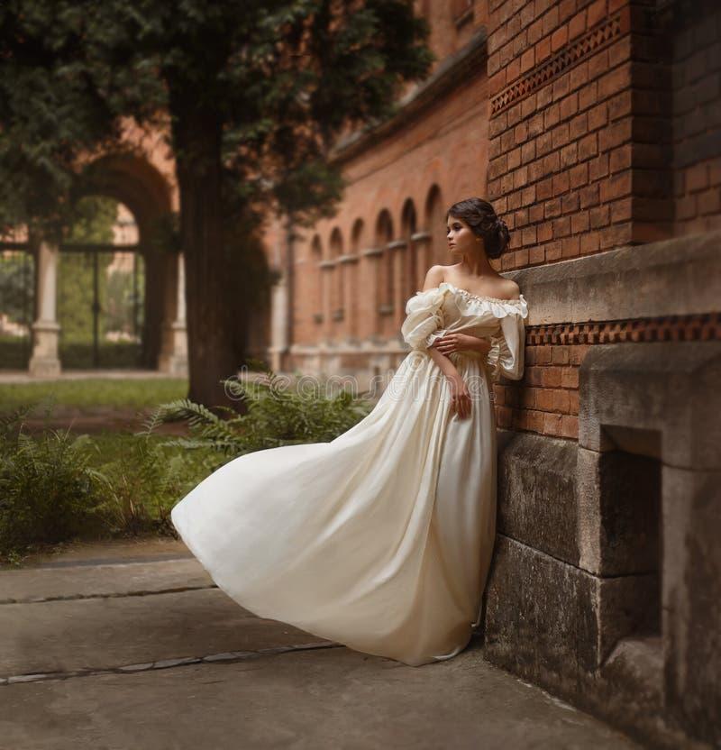 Una giovane signora sta alla parete di un castello antico che guarda con la speranza nella distanza Emozione che aspetta il lungo immagini stock libere da diritti