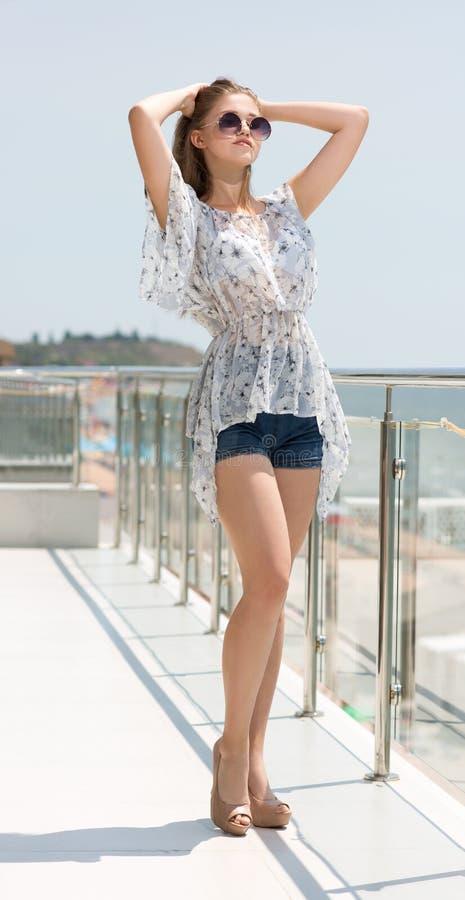 Una giovane signora in una blusa leggera e pantaloncini corti su un balcone del ` s dell'hotel Una ragazza affascinante con capel fotografia stock