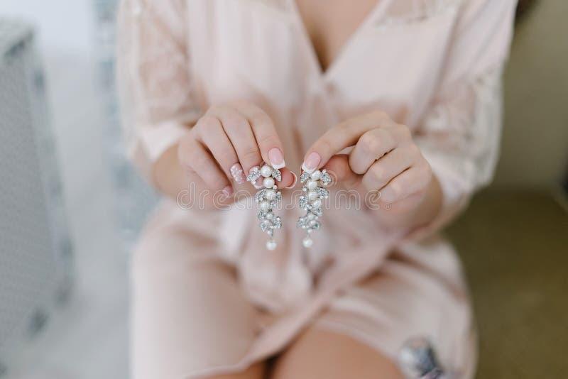 Una giovane sposa tiene gli orecchini in sue mani immagine stock libera da diritti
