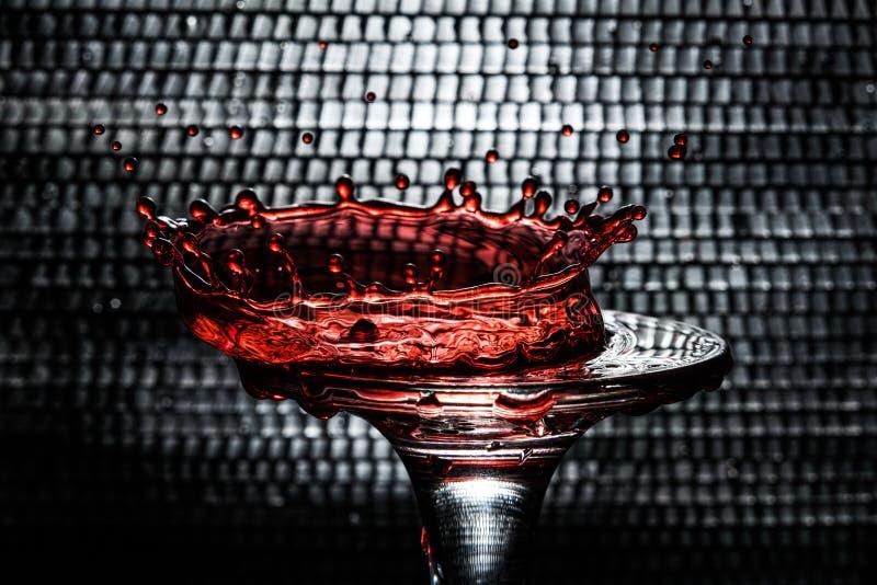 Una goccia di vino rosso sotto forma di corona che è caduto su un calice di vetro fotografia stock