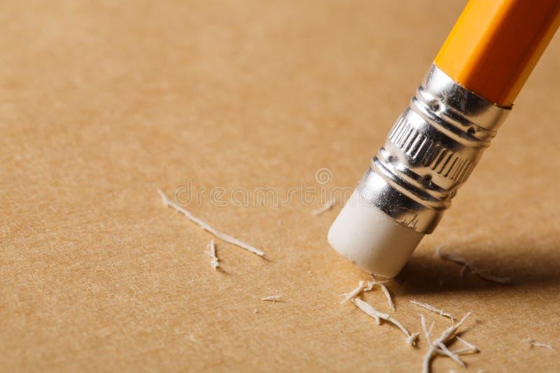 Una gomma di matita che rimuove un errore scritto su pezzo di carta immagine stock