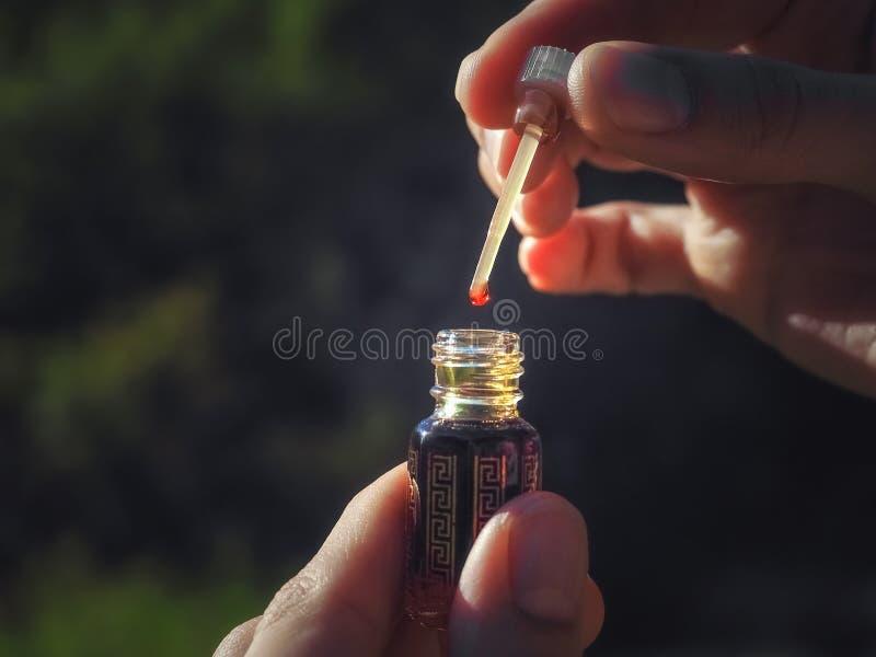 Una gota de petróleo del Oud Fragancias de aroma arábigo de argamasa o de aceite de agarwood en minibotellas foto de archivo