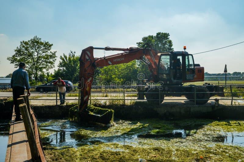 Una grúa actuada hombre del excavador quita la ruina y las algas se acumulan del canal de Naviglio Pavese en un día soleado fotos de archivo libres de regalías