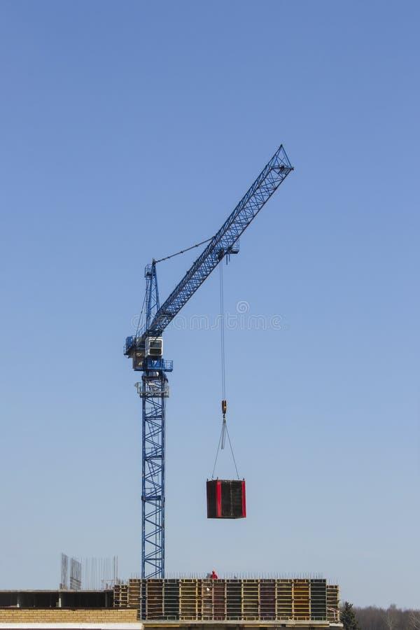 Una grúa de construcción mueve la carga Materiales de construcción en las plataformas Construcci?n de un edificio residencial mod fotografía de archivo libre de regalías