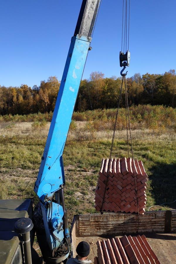 Una grúa del camión descarga los ladrillos para construir una casa imagen de archivo