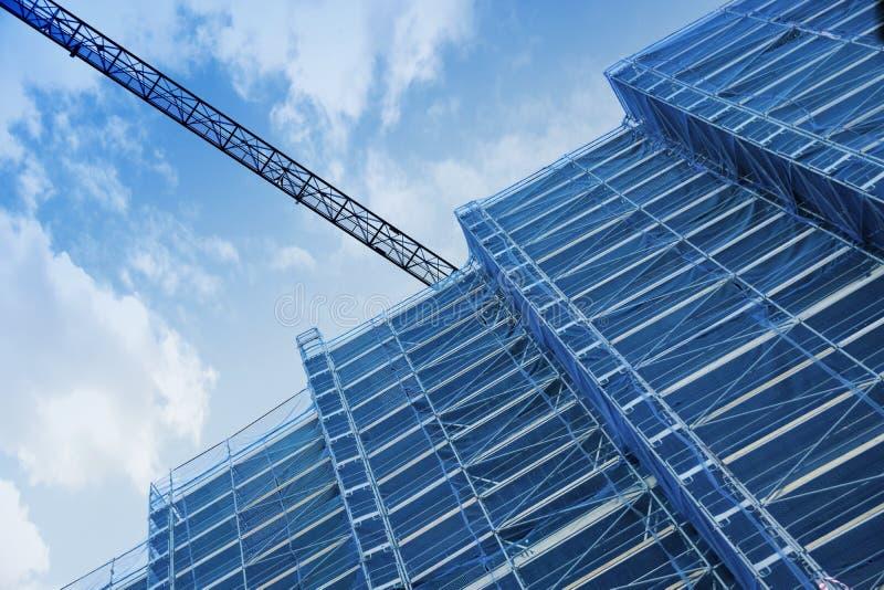 Una grúa en una construcción Estructura alta del andamio de debajo imagen de archivo libre de regalías