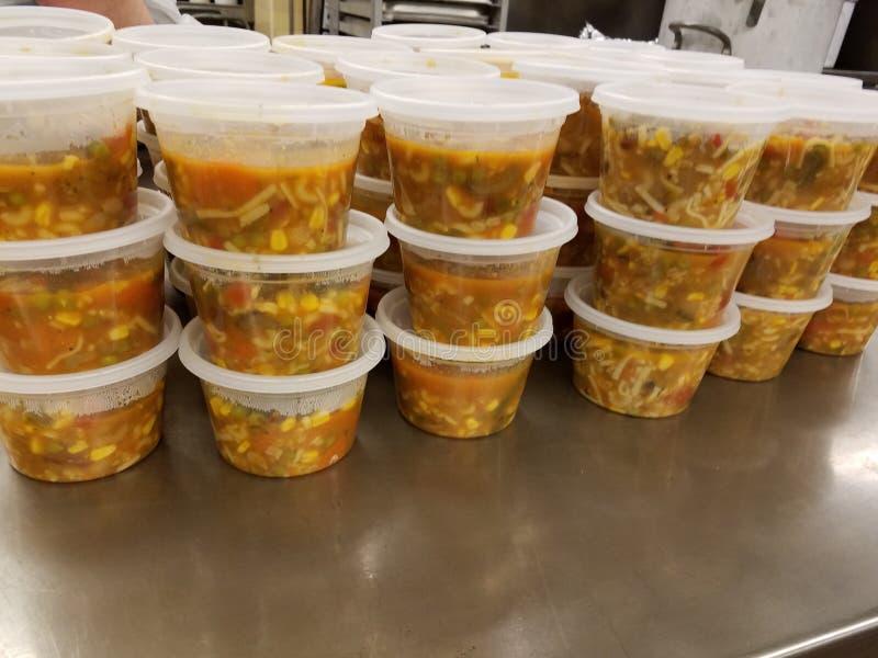 Una gran cantidad de alimento cocido en envases de plástico en la tabla del metal en cocina industrial fotografía de archivo