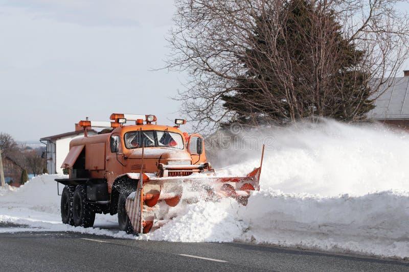 Una grande automobile con un aratro rimuove la strada da neve L'attrezzatura speciale del carico arancio sta lottando con gli ele immagine stock
